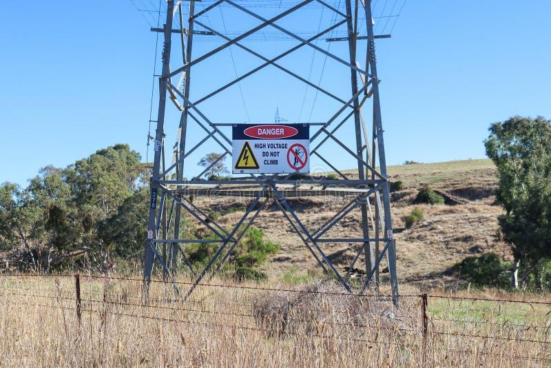 Röd svartvit fara, klättrar inte varningstecknet på ett elektricitetsöverföringstorn i lantliga Australien arkivbilder