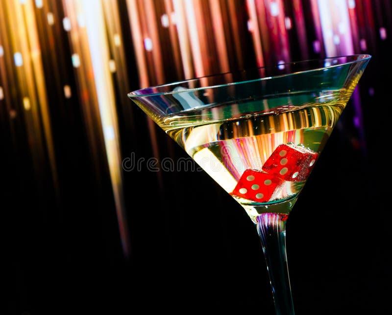 Röd tärning i coctailexponeringsglaset på färgrik lutning arkivfoton