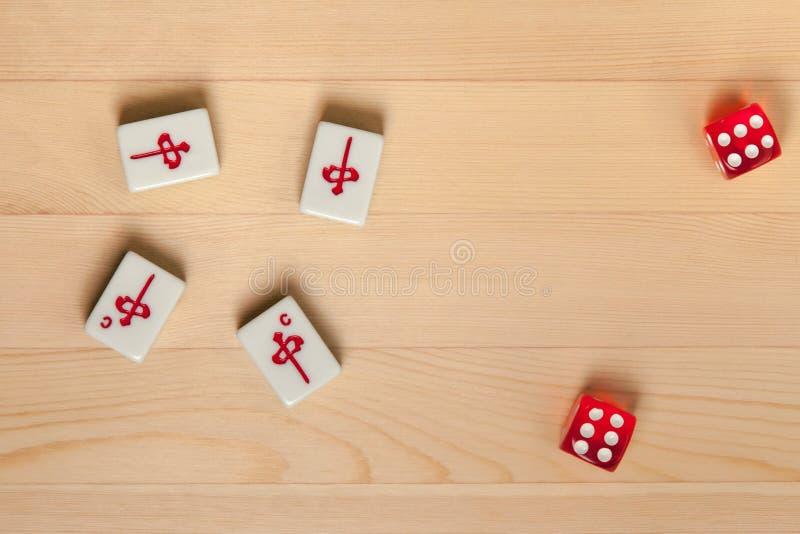 Röd tärning och bentegelplattor för mahjong på ett ljust - brun träbakgrund royaltyfri fotografi