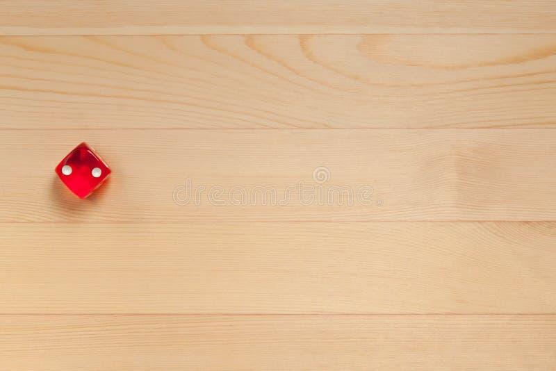 Röd tärning på ett ljust - brun träbakgrund Kasserade 5 royaltyfri bild
