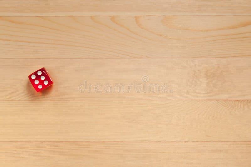 Röd tärning på ett ljust - brun träbakgrund Kasserade 5 royaltyfri fotografi