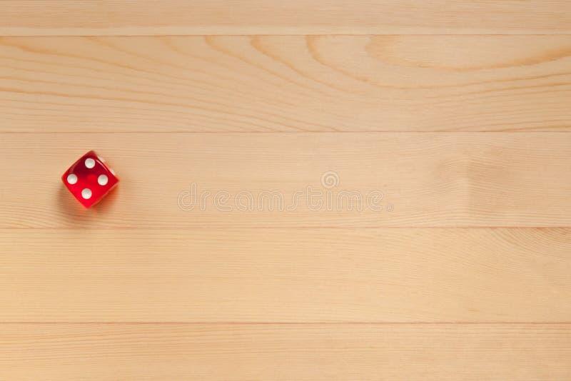 Röd tärning på ett ljust - brun träbakgrund Kasserade 5 arkivbilder