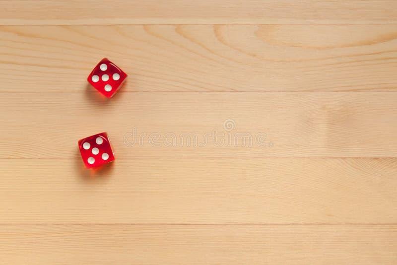 Röd tärning på ett ljust - brun träbakgrund Kasserat 10 5 och 5 royaltyfri bild