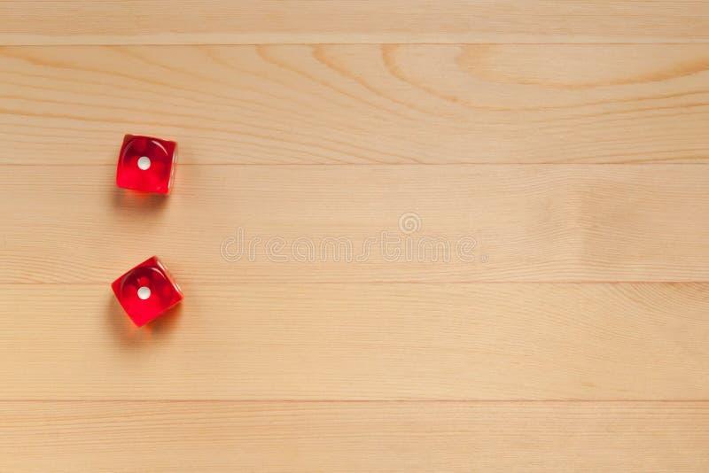 Röd tärning på ett ljust - brun träbakgrund Kasserat 2 1 och 1 royaltyfri foto