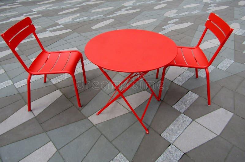 Röd tabell och två stolar arkivfoton