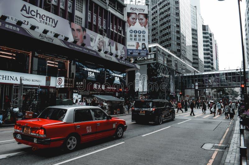 Röd taxi på en upptagen övergångsställe på gatan i Hong Kong China arkivfoton