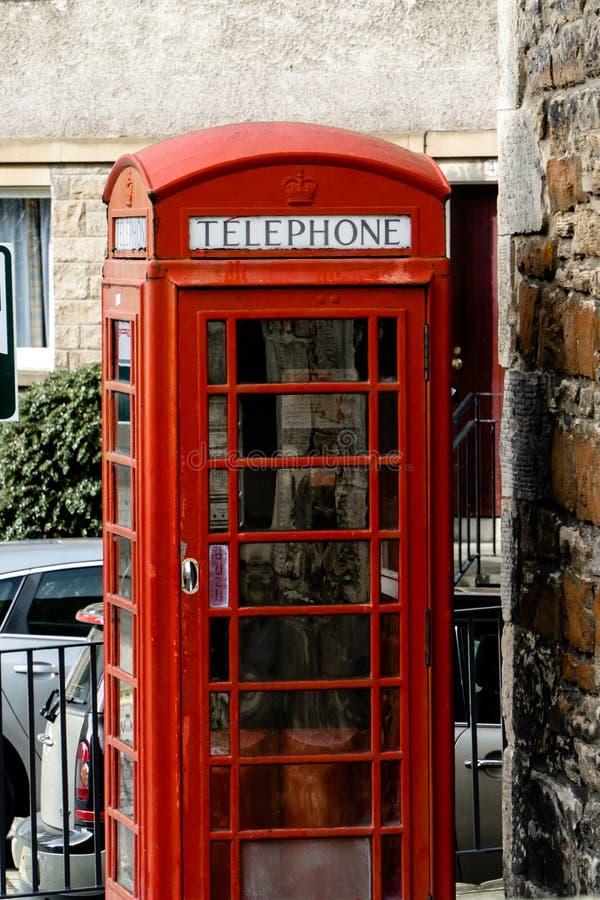 Röd telefonask i en by arkivbild
