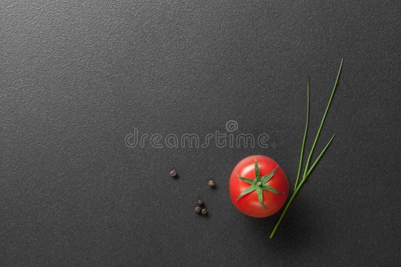 Röd tomat med salladslöken på svart royaltyfri bild