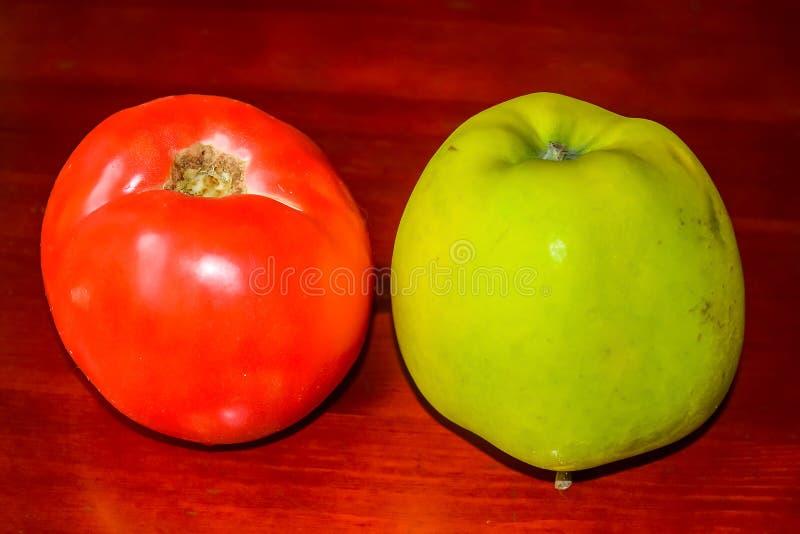 Röd tomat och ett grönt äpple arkivfoton
