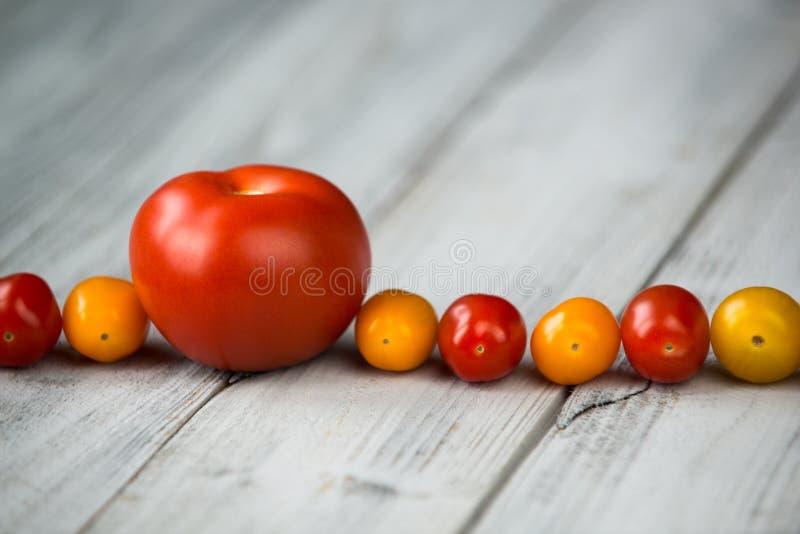 Röd tomat och körsbärsröda röda och gula tomater i en linje på en träbakgrund arkivfoto