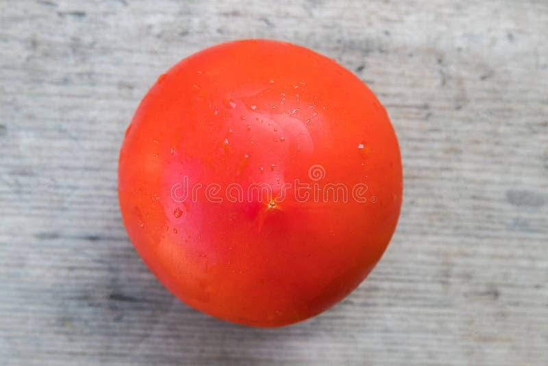Röd tomat på ett grått träbräde royaltyfri bild