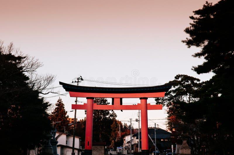 Röd Torii port på den Morioka Hachimangu relikskrin i Iwate på solnedgången med varm signalhimmel fotografering för bildbyråer