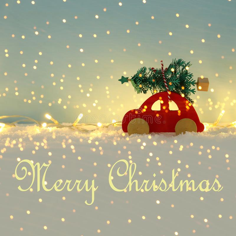 Röd träbil som bär ett julträd över insnöad framdel av blå bakgrund och guld- girlandljus arkivfoto