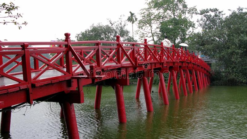 Röd träbro vid den blåa sjön arkivfoto