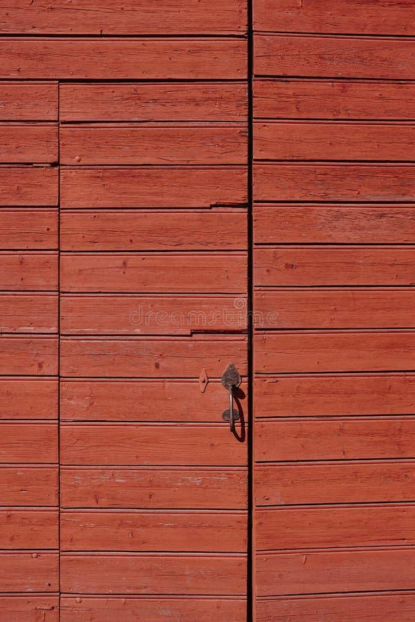 Röd trärostad och stängd dörrdetalj lantlig bakgrund arkivbild