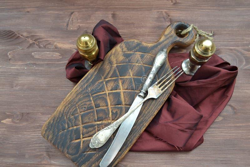 Röd träskärbräda med silverpepperboxen och gaffel på mörk bakgrund Brun sjaskig trätabell Begreppet av sunt bantar royaltyfri foto
