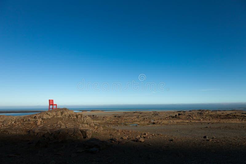 Röd trästol på ett tomt stenigt landskap i Island arkivbilder