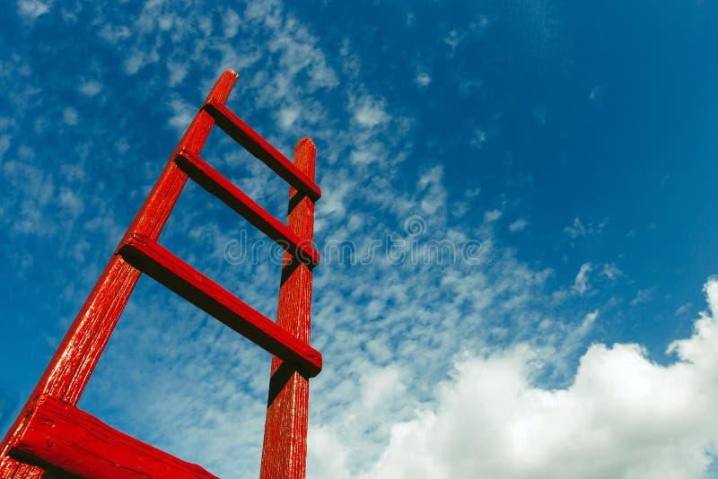 Röd trätrappuppgång mot den blåa himlen Begrepp för tillväxt för himmel för karriär för utvecklingsmotivationaffär arkivfoton