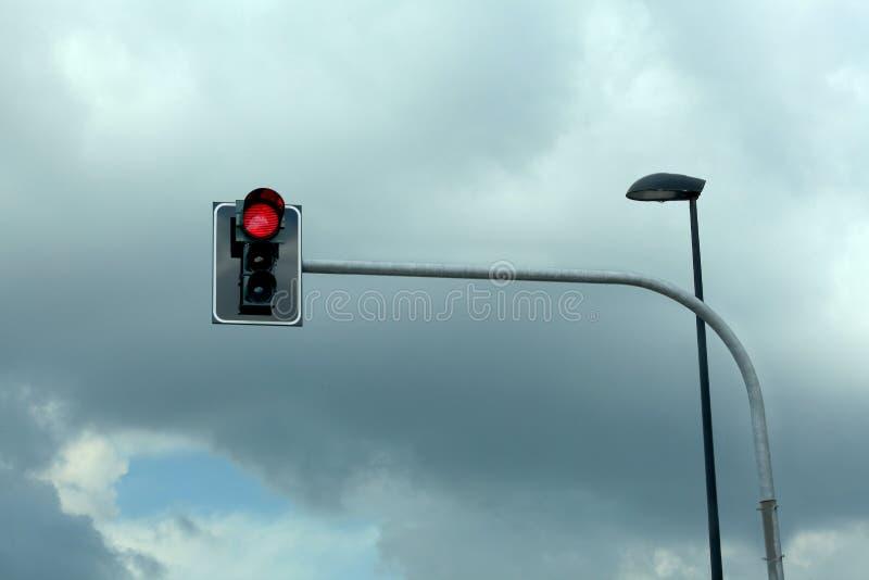 Röd trafikljus på en bakgrund för molnig himmel med kopieringsutrymme för din text royaltyfria bilder