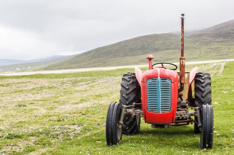 Röd traktor för tappning i ett fält i UK royaltyfri fotografi