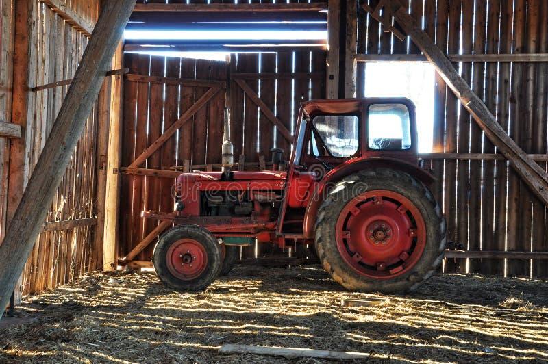 Röd traktor i ladugård arkivbild