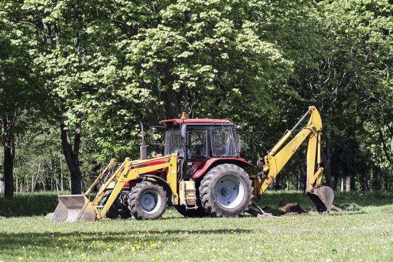 Röd traktor och gräsklippare, saxgräsmattor i gränderna i parkera arkivfoto