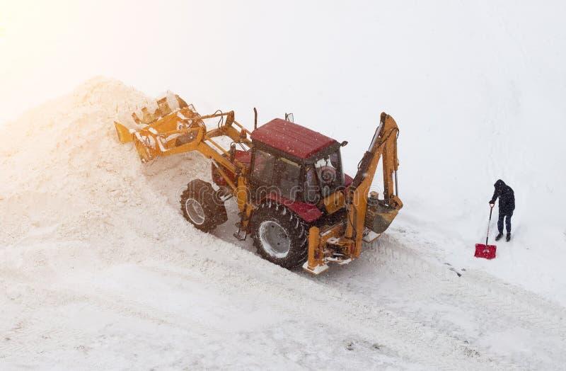 Röd traktor och man med en skyffel på snölokalvård arkivbild