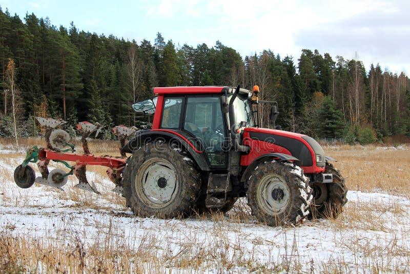 Röd traktor på fält i tidig vinter arkivfoton