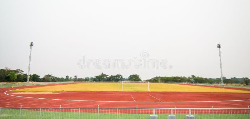 Röd trampkvarn, spårspring och fotbollfält på stadion w arkivfoton