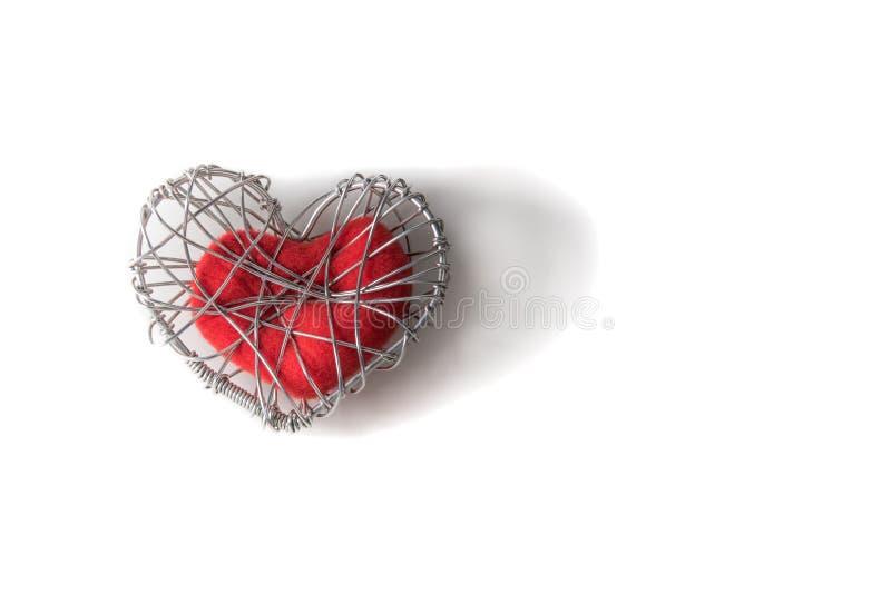 Röd tyghjärta i stucken trådbur royaltyfri bild