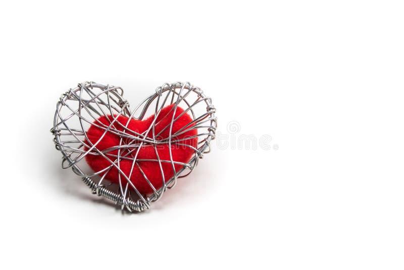 Röd tyghjärta i stucken trådbur royaltyfri foto