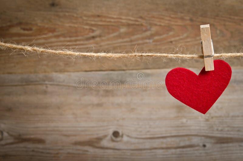 Röd tyghjärta som hänger på klädstrecket royaltyfri foto