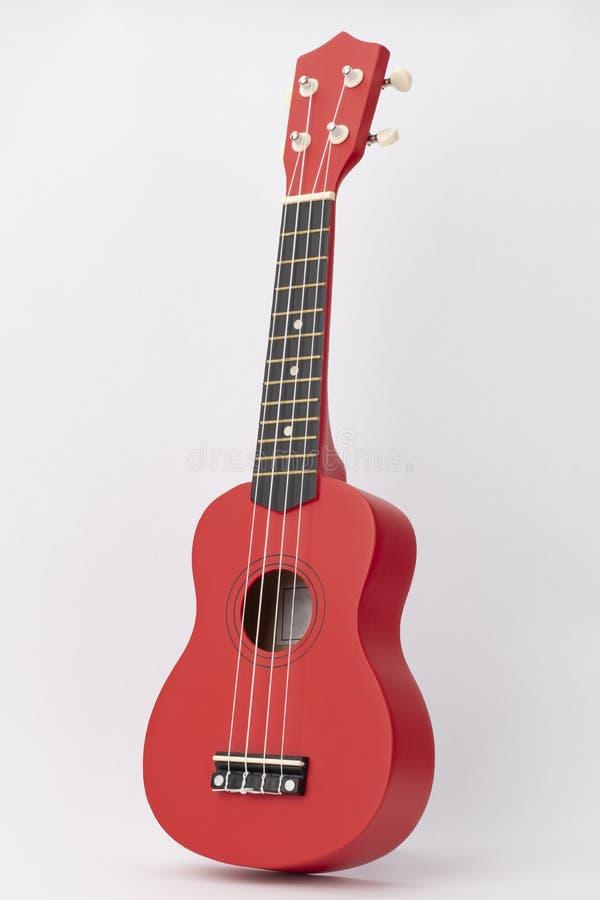 Röd ukulele med vita rader fotografering för bildbyråer