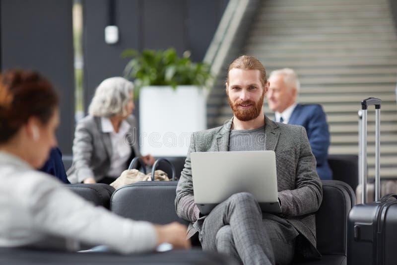 Röd-uppsökt entreprenör som använder bärbara datorn i flygplats royaltyfri fotografi