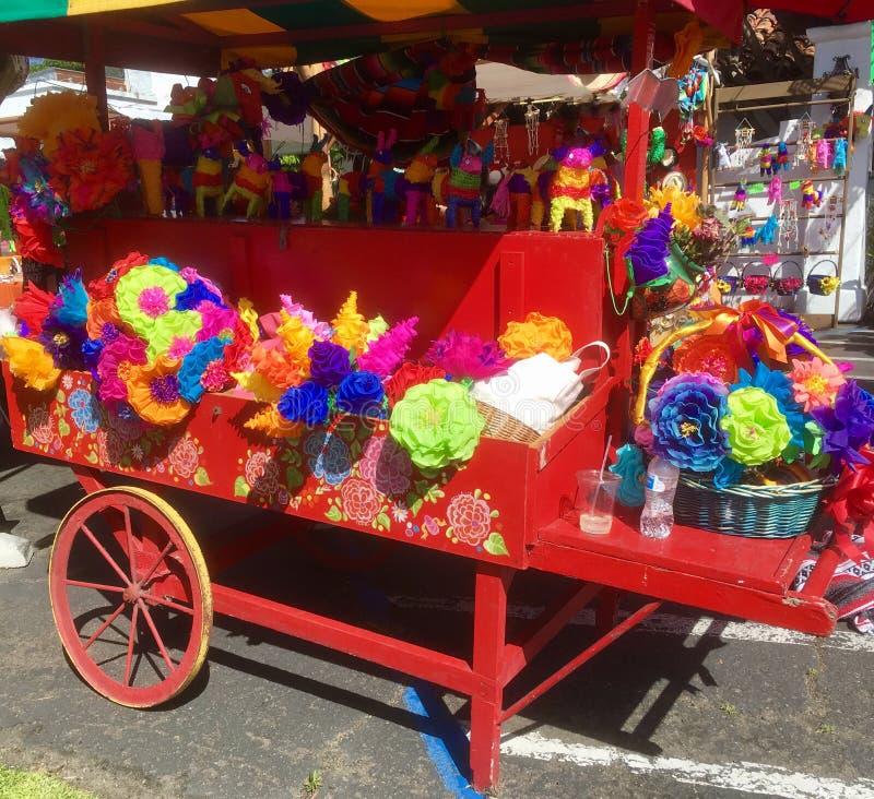 Röd vagn med pappers- blommor royaltyfri fotografi