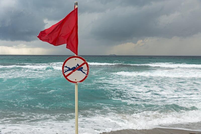 Röd varnande flagga på havsstranden arkivfoton