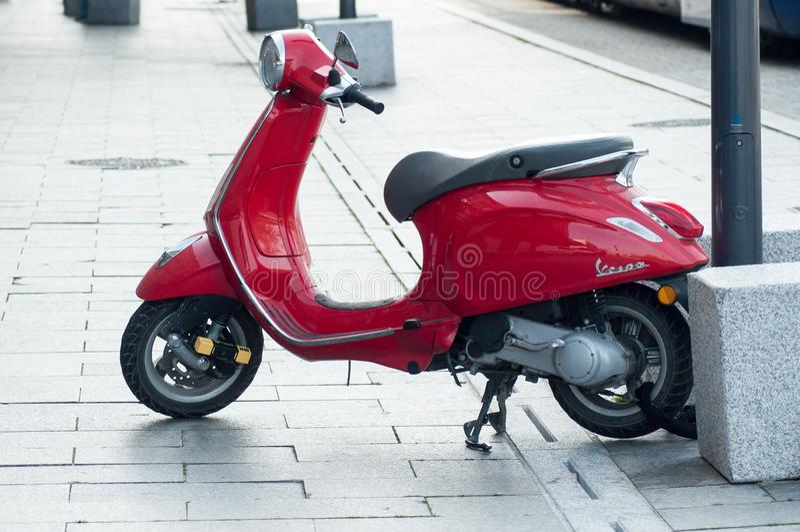 röd vespasparkcykel nära drevstationen arkivfoton