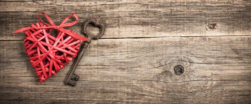 Röd vide- hjärta- och tappningtangent på träbakgrund royaltyfri fotografi