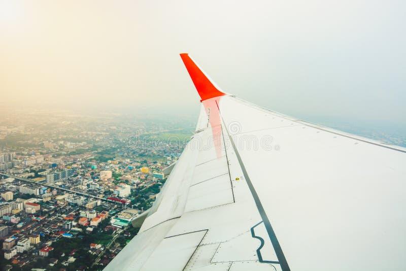 Röd vinge av flygplansikten från flygplanfönsterplats under tagande av och flyg ovanför stadslandskap med solljusbakgrund royaltyfri foto