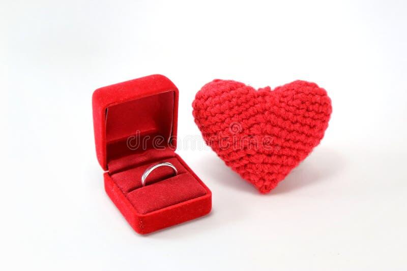 Röd virkad hjärta med vigselringen i en ask på isolerad vit bakgrund valentin för dag s Symbol av förälskelse royaltyfria bilder