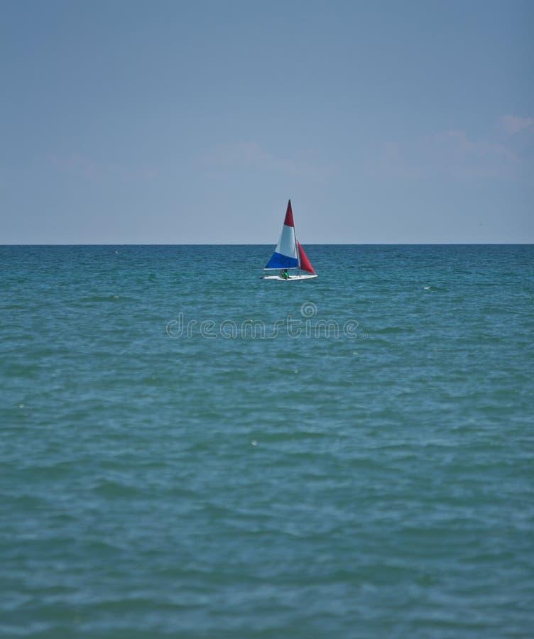 Röd, vit- och blåttsegelbåt fotografering för bildbyråer