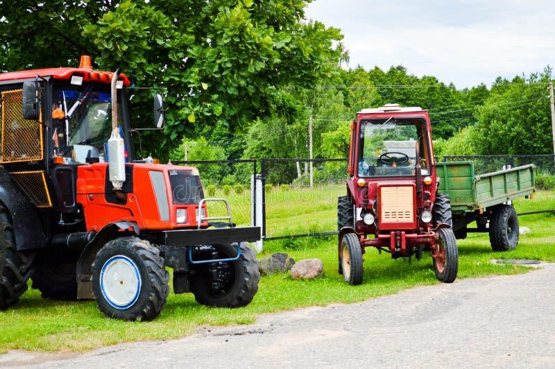 Röd yrkesmässig jordbruks- traktor för konstruktion två med stora hjul med en däckmönster för att ploga fältet, land, trans. arkivbild