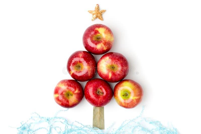 Röda äpplen ligger i form av en julgran på en vit royaltyfri foto