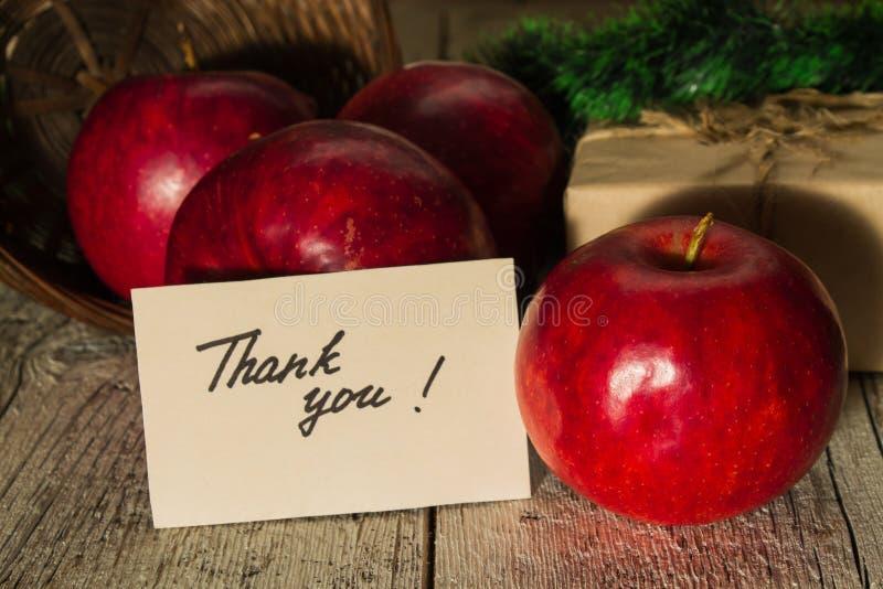 Röda äpplen med en gåva och ett kort fotografering för bildbyråer