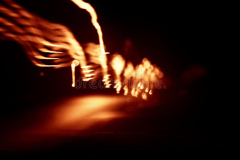Röda abstrakta slingor av ljus på mörk bakgrund arkivbilder