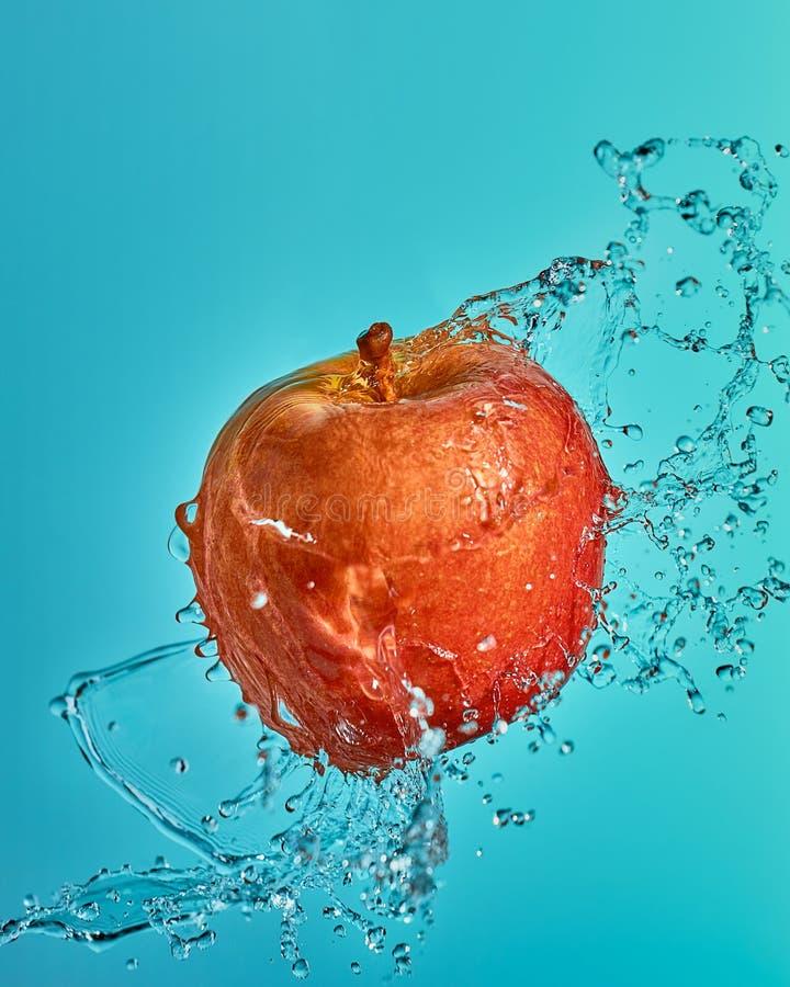 Röda Apple i flygasprejen av vatten royaltyfri fotografi