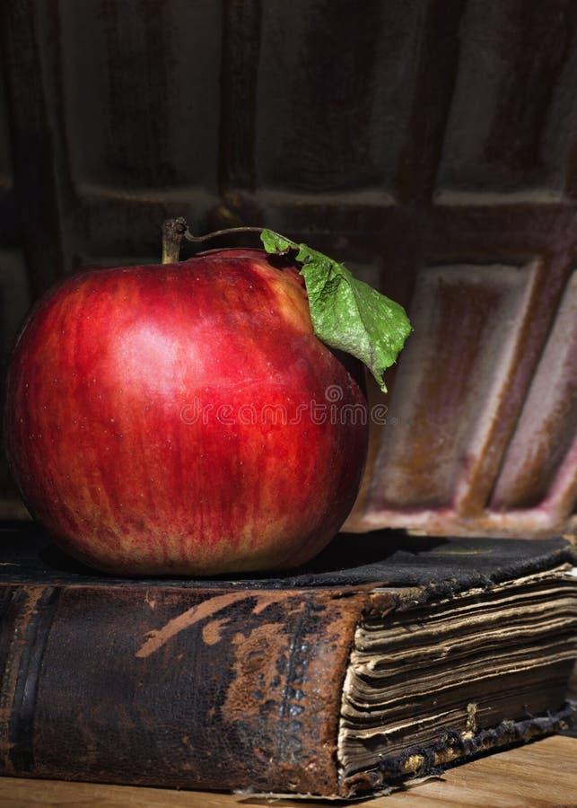 Röda Apple med det gröna bladet på den gamla boken royaltyfri foto