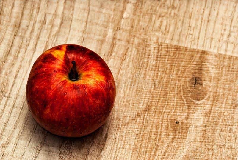 Röda Apple på en träbakgrund arkivfoto