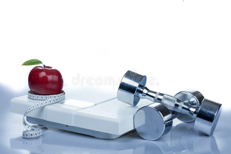 Röda Apple som mäter bandet, hantlar och vikt royaltyfri bild