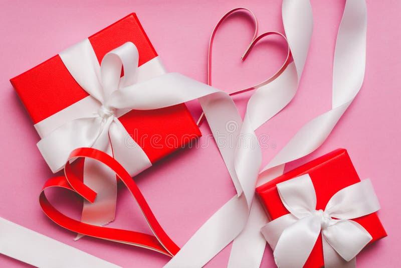 Röda askar med en gåva som binds med ett vitt band och röda hemlagade pappers- hjärtor på en rosa bakgrund Symbol av dagen för va arkivbild